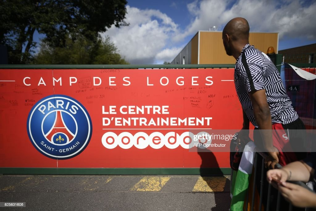 Fans wait in front of the entrance of the Paris Saint-Germain's (PSG) Camp des Loges training centre in Saint-Germain-en-Laye, western Paris on August 3, 2017, as Brazilian football player Neymar is expected to arrive in Paris to finalise his world-record transfer from Barcelona to PSG. Neymar is expected to arrive in Paris on August 3 to finalise his world record 222 million euro ($260 million) move from Barcelona to Paris Saint-Germain, which will earn him around 30 million euros ($35.5 million) a year. / AFP PHOTO / Lionel BONAVENTURE