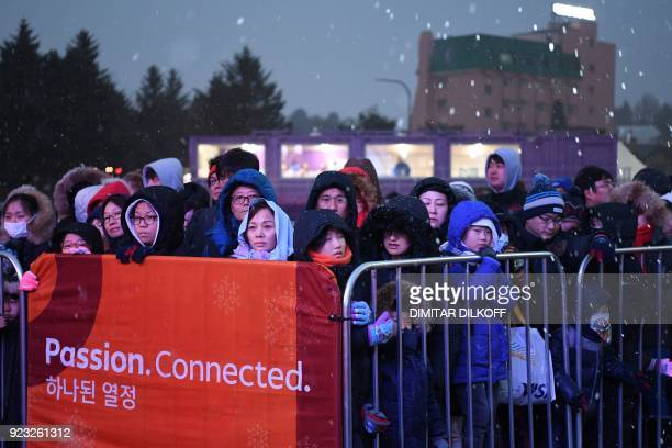 Fans wait under the snow for the start of the medal ceremonies at the Pyeongchang Medals Plaza during the Pyeongchang 2018 Winter Olympic Games in...