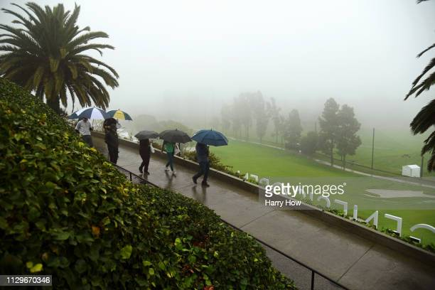 Fans walk along the course as play is suspended due to rain during the first round of the Genesis Open at Riviera Country Club on February 14 2019 in...