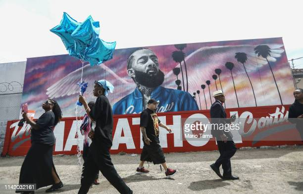 Fans walk as they wait outside The Marathon Clothing store for the funeral procession for slain rapper Nipsey Hussle on April 11 2019 in Los Angeles...