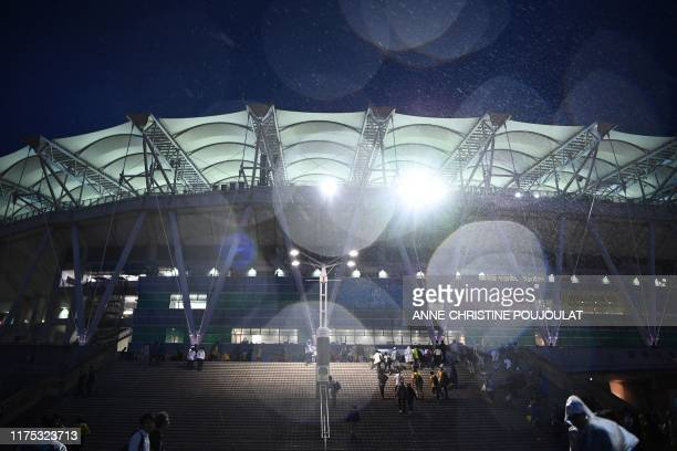 Fans walk in the rain as they arrive for the Japan 2019 Rugby World Cup Pool D match between Australia and Georgia at the Shizuoka Stadium Ecopa in...