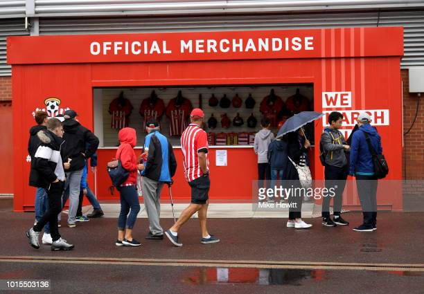 Fans walk merchandise for sale prior to the Premier League match between Southampton FC and Burnley FC at St Mary's Stadium on August 12 2018 in...