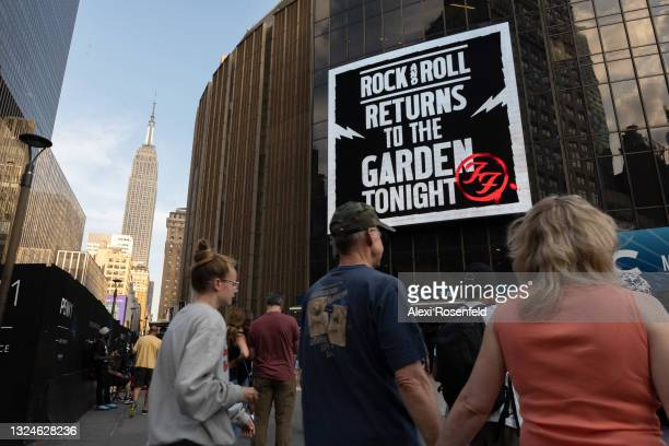 """Fans walk past a digital display that reads, """"rock and roll returns to the Garden tonight"""" at the Foo Fighters concert at Madison Square Garden with..."""