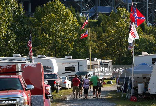 NASCAR fans walk past a pair of Confederate flags and a Trump flag as they make their way to the Bass Pro Shops NRA Night Race in Bristol TN on Aug...