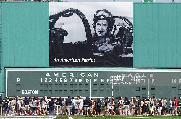 Fans walk past a poster of Ted Williams during his military service in Korea sitting in his fighter jet hanging over the Green Monster before the Ted...