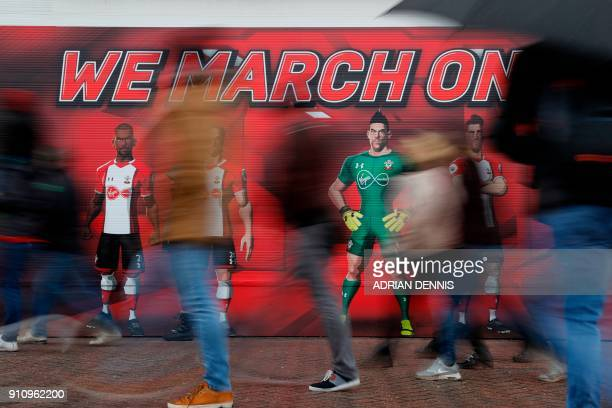 Fans walk past a wall outside the stadium adorned with a message to 'We March On' ahead of kick off of the English FA Cup fourth round football match...