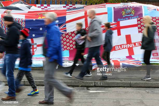 Fans walk past flags as they arrive at the stadium prior to the Premier League match between Burnley FC and Huddersfield Town at Turf Moor on October...