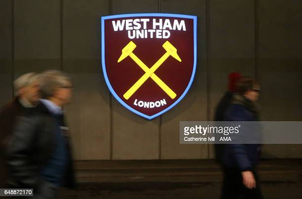 Fans walk past the West Ham United club badge / crest before the Premier League match between West Ham United and Chelsea at London Stadium on March...