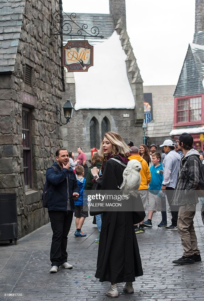 Fans walk through Hogsmeade at the Grand Opening to the public of the 'Wizarding World of Harry Potter' at Universal Studios Hollywood, in Universal City, California, on April 7, 2016. Fifteen years after Harry Potter's first big screen adventure, Universal is enchanting a new generation of Muggles with its most spectacular conjuring trick yet -- a theme park in the heart of Hollywood. / AFP / VALERIE