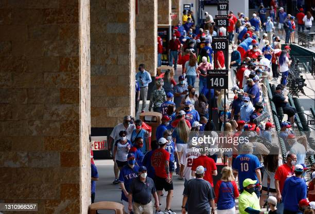 Fans walk to their seats during batting practice before the Texas Rangers take on the Toronto Blue Jays in the Rangers home opener at Globe Life...