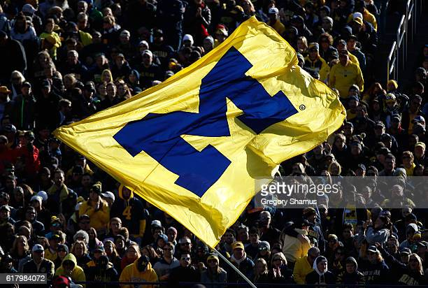 Fans watch a Michigan Wolverines flag after a score against the Illinois Fighting Illini on October 22 2016 at Michigan Stadium in Ann Arbor Michigan
