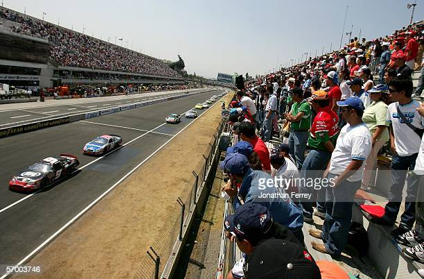Fans watch a pack of cars race by during the NASCAR Busch Series Telcel-Motorola 200 on March 5, 2006 at Autodromo Hermanos Rodriguez in Mexico City,...