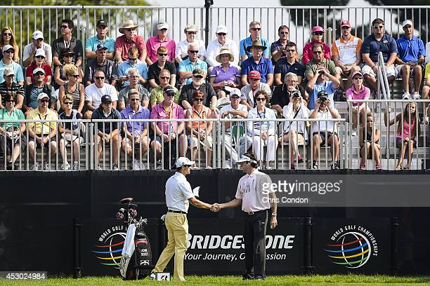 Fans watch as Adam Scott of Australia shakes hands with Bubba Watson on the 10th hole tee box before starting the second round of the World Golf...