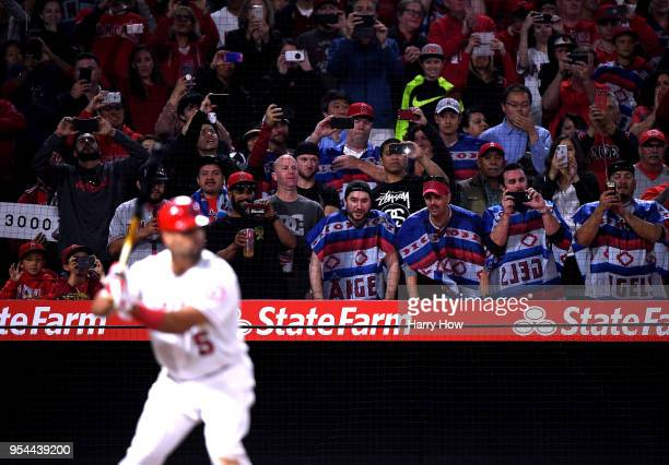 Fans watch as Albert Pujols of the Los Angeles Angels waits for a pitch with 2999 career hits during the ninth inning against the Baltimore Orioles...