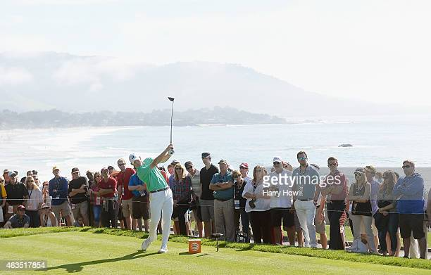 Fans watch as Brandt Snedeker hits his tee shot on the 14th hole during the final round of the ATT Pebble Beach National ProAm at the Pebble Beach...