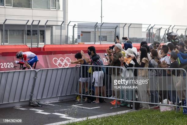 Fans watch as France's Remi Cavagna passes along the circuit during the men's cycling road individual time trial during the Tokyo 2020 Olympic Games...