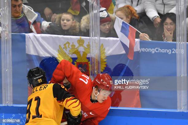 Fans watch as Germany's Moritz Muller and Russia's Kirill Kaprizov collide in the men's gold medal ice hockey match between the Olympic Athletes from...