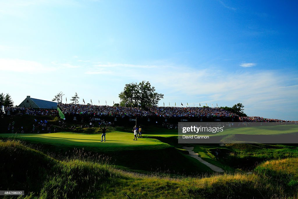 Fans watch as Jason Day of Australia celebrates on the 18th green after winning the 2015 PGA Championship with a score of 20-under par at Whistling Straits on August 16, 2015 in Sheboygan, Wisconsin.