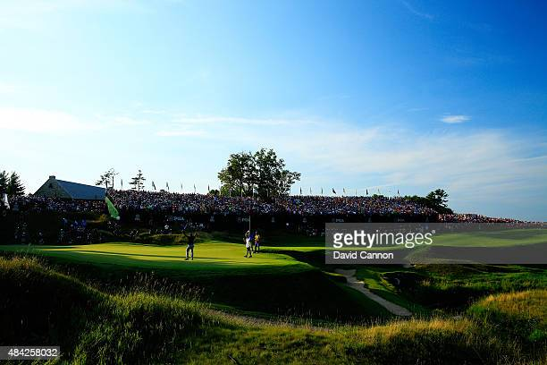 Fans watch as Jason Day of Australia celebrates on the 18th green after winning the 2015 PGA Championship with a score of 20-under par at Whistling...
