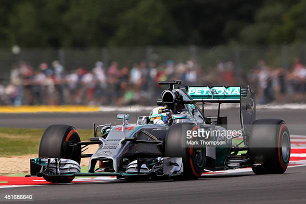 Fans watch as Lewis Hamilton of Great Britain and Mercedes GP drives during practice ahead of the British Formula One Grand Prix at Silverstone...