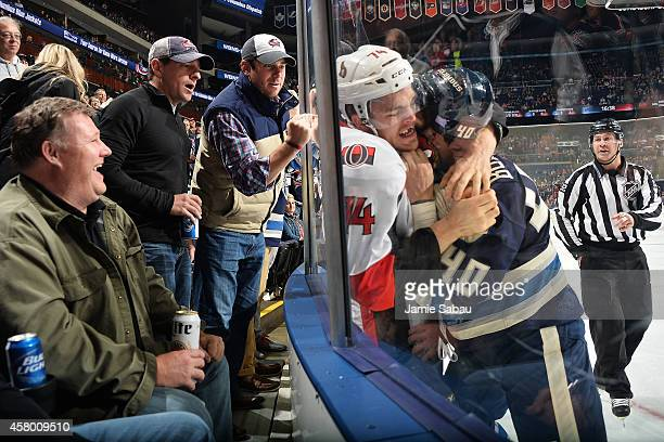 Fans watch as Mark Borowiecki of the Ottawa Senators and Jared Boll of the Columbus Blue Jackets fight against the glass during the first period on...