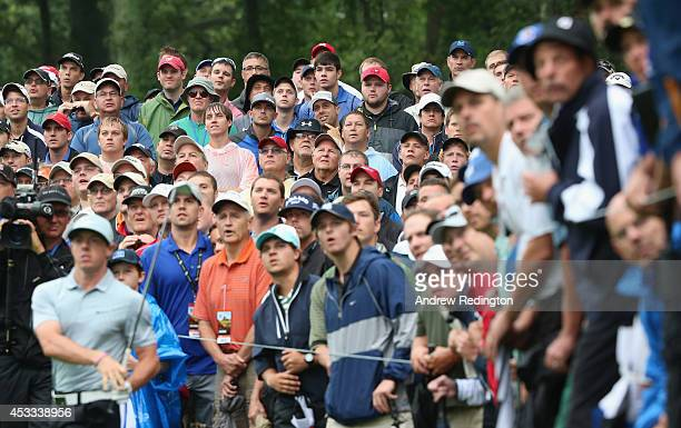Fans watch as Rory McIlroy of Northern Ireland hits a shot from the rough on the 12th hole during the weatherdelayed second round of the 96th PGA...