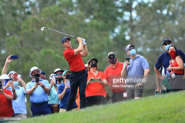 Fans watch as Rory McIlroy of Northern Ireland hits an approach shot on the seventh hole during the final round of World Golf Championships-Workday...