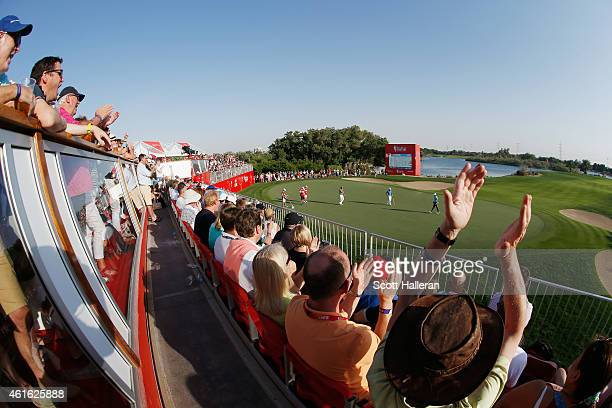 Fans watch as Rory McIlroy of Northern Ireland saves his par on the 17th hole during the second round of the Abu Dhabi HSBC Golf Championship at the...