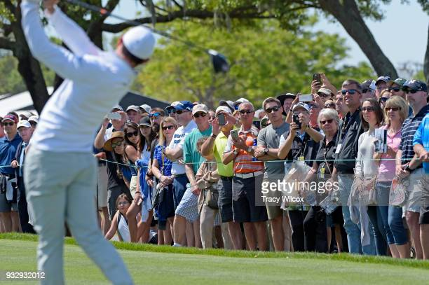 Fans watch as Rory McIlroy of Northern Ireland tees off on hole No 9 during the second round of the Arnold Palmer Invitational presented by...