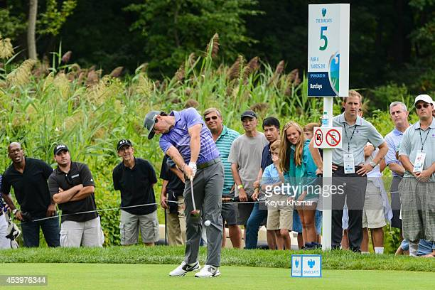 Fans watch as Rory McIlroy of Northern Ireland tees off on the fifth hole during the second round of The Barclays at Ridgewood Country Club on August...