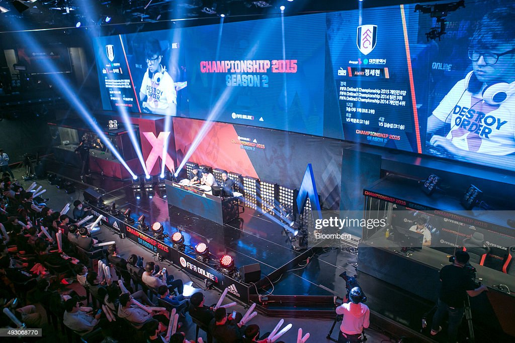 Fans watch as screens show Jeong Se Hyun, a professional video-game player, competing against Yang Jin Hyeob, not pictured, during the final round of the Electronic Arts Inc. (EA) Sports FIFA Online Championship at the Nexon Co. e-Sports Stadium in Seoul, South Korea, on Saturday, Oct. 17, 2015. Video game competitions, known as eSports, have been expanding as gamers seek to shift perceptions around their craft from a basement hobby to a serious money making industry. Photographer: Jean Chung/Bloomberg via Getty Images