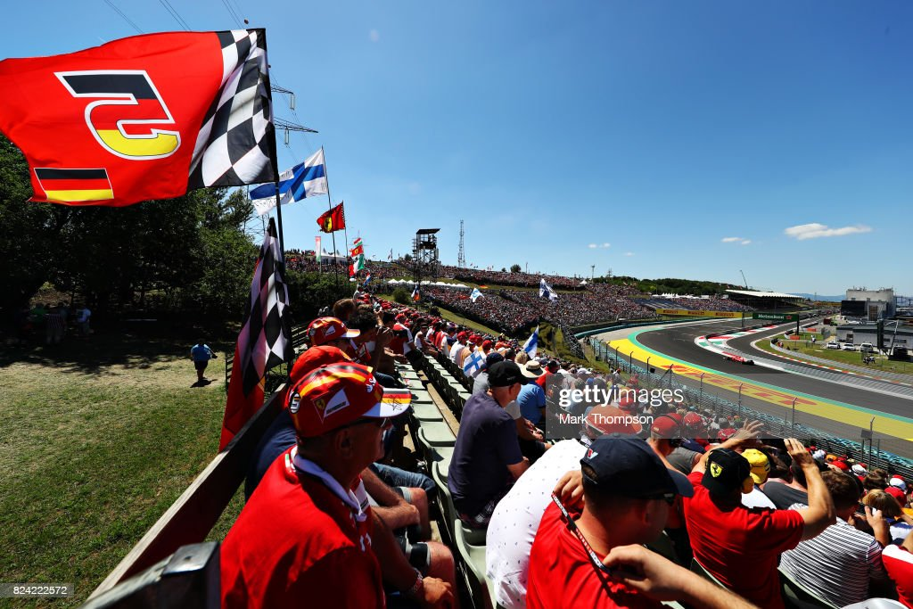 Fans watch as Sebastian Vettel of Germany driving the (5) Scuderia Ferrari SF70H rounds the last corner during qualifying for the Formula One Grand Prix of Hungary at Hungaroring on July 29, 2017 in Budapest, Hungary.
