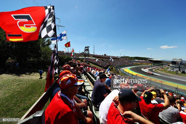 Fans watch as Sebastian Vettel of Germany driving the Scuderia Ferrari SF70H rounds the last corner during qualifying for the Formula One Grand Prix...