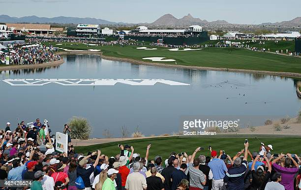 Fans watch as Tiger Woods hits his tee shot on the 18th hole during the proam prior to the start of the Waste Management Phoenix Open at TPC...