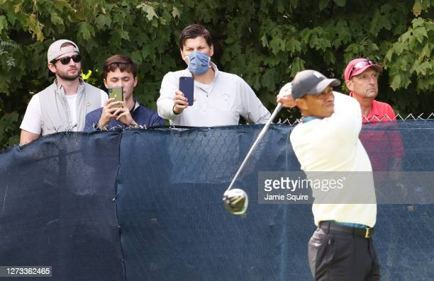 Fans watch as Tiger Woods of the United States plays his shot from the 12th tee during the second round of the 120th U.S. Open Championship on...