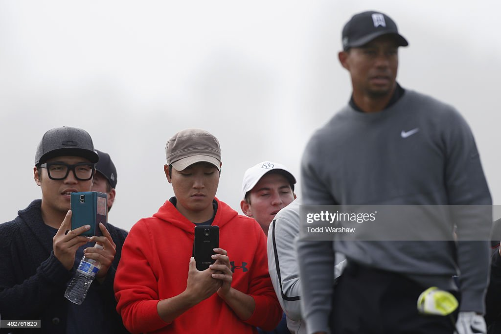 Fans watch as Tiger Woods (R) tees off on the fourth hole of the North Course during the Farmers Insurance Open Pro Am at Torrey Pines Golf Course on February 4, 2015 in San Diego, California.