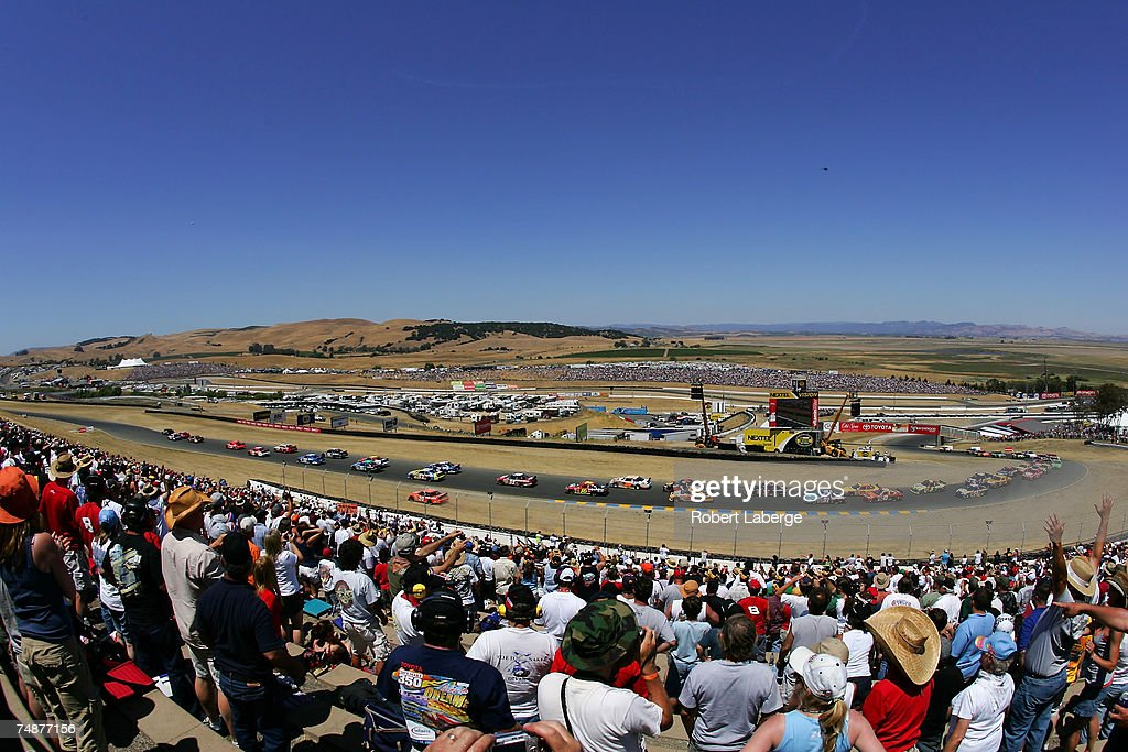 Fans watch as Tony Stewart, driver of the #20 The Home Depot Chevrolet, drives off the track on the first lap of the NASCAR Nextel Cup Series Toyota/Save Mart 350 at Infineon Raceway on June 24, 2007 in Sonoma, California.
