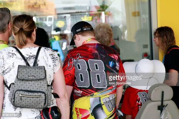 Fans watch drivers and crews work on their car in the Neon Garage for the Kobalt 400 at the Las Vegas Motor Speedway in Las Vegas NV
