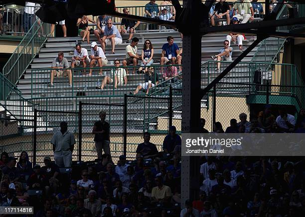 Fans watch from a roof top across from Wrigley Field as the Chicago Cubs take on the New York Yankees on June 17 2011 in Chicago Illinois The Cubs...