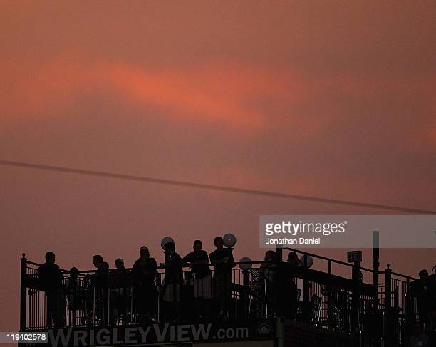 Fans watch from a rooftop across the street from Wrigley Field as the Chicago Cubs take on the Philadelphia Phillies on July 19 2011 in Chicago...