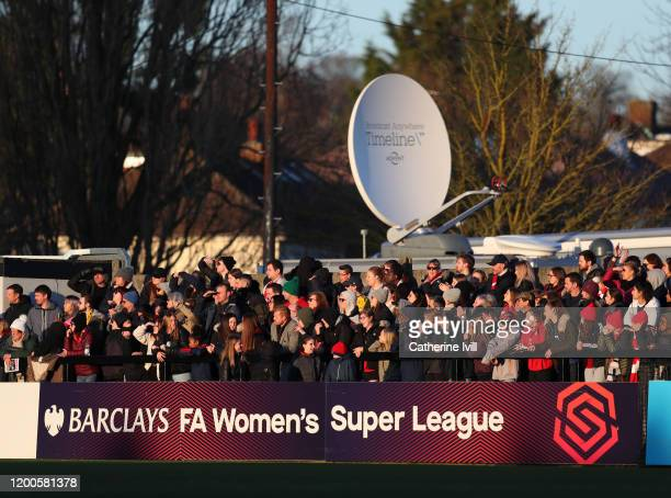 Fans watch from behind the advertising board during the Barclays FA Women's Super League match between Arsenal and Chelsea at Meadow Park on January...