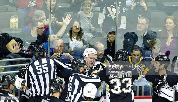 Fans watch from behind the glass as players from the Los Angeles Kings and Pittsburgh Penguins tussle during Tuesday's preseason hockey game on...