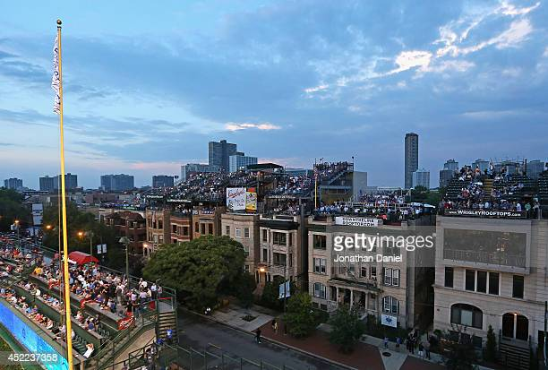 Fans watch from roof tops over right field as the Chicago Cubs take on the Cincinnati Reds at Wrigley Field on June 24 2014 in Chicago Illinois The...