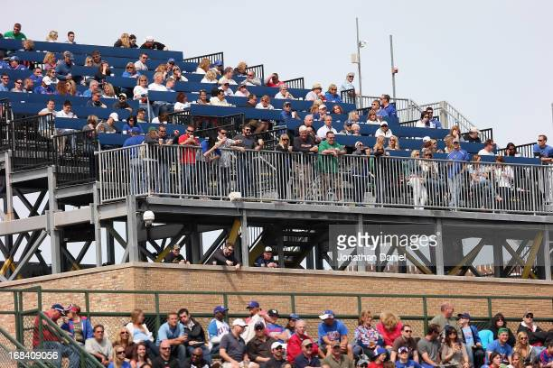 Fans watch from rooftops outside Wrigley Field as the Chicago Cubs take on the Cincinnati Reds on May 5 2013 in Chicago Illinois The Reds defeated...