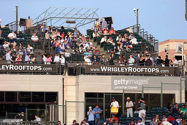 Fans watch from the roof tops across the street from Wrigley Field as the Chicago Cubs take on the New York Mets at Wrigley Field on June 5 2014 in...