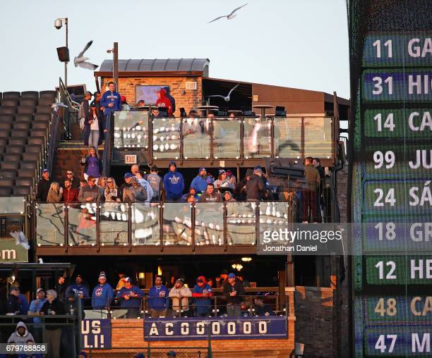 Fans watch from the rooftop as the Chicago Cubs take on the New York Yankees at Wrigley Field on May 6 2017 in Chicago Illinois