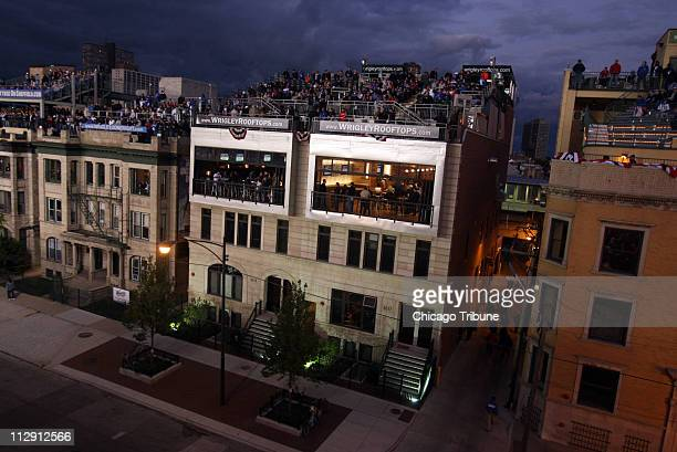 Fans watch Game 1 of the National League Division Series between the Chicago Cubs and Los Angeles Dodgers from the roofs and porches of apartments...