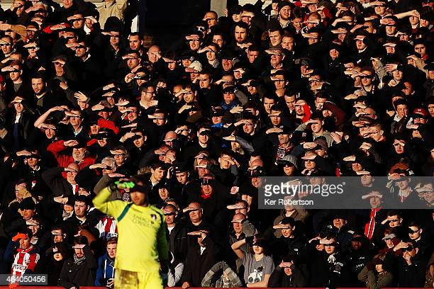 Fans watch in the winter sunshine during the Sky Bet Championship match between Brentford and AFC Bournemouth at Griffin Park on February 21 2015 in...