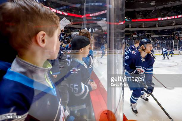 Fans watch intently as Kyle Connor of the Winnipeg Jets takes part in the pregame warm up prior to NHL action against the Dallas Stars at the Bell...