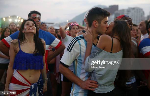 S fans watch next to a couple kissinf during the first half of their match against Belgium at FIFA Fan Fest on Copacabana Beach during the 2014 FIFA...